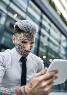 Young businessman with tattooed face, using digital tablet - ZEDF01343