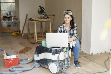 Young woman renovating her new flat, using laptop - PESF01073