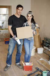 Happy couple renovating their new home, holding cardboard sign - PESF01082