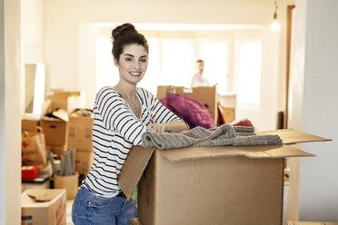 Young woman moving house, unpacking cardboard boxes - PESF01088