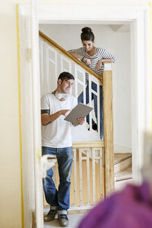 Young couple standing on staircase, using digital tablet, renovating their house - PESF01091