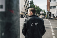 Back view of young man wearing black leather jacket with writing 'Love' - GUSF00715