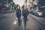 Young couple wearing black matching clothes walking side by side on the street - GUSF00718