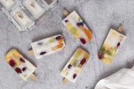 Homemade fruits and yogurt ice lollies on marble - RTBF01211