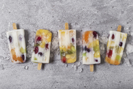 Homemade fruits and yogurt ice lollies on marble - RTBF01214