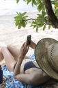 Young lying woman on the beach, using smartphone - KNTF01121