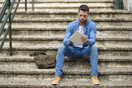 Young man sitting on stairs, working, using digital tablet - JSMF00144