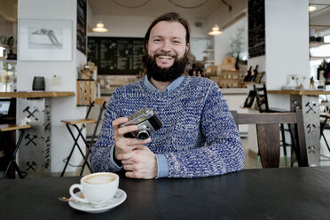 Man with beard sitting in cafe, holding old camera - FLLF00005