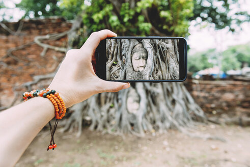 Thailand, Ayutthaya, Wat Mahathat,  woman taking a picture with smartphone of buddha head in tree roots - GEMF01913