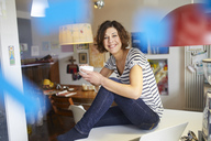 Portrait of happy mature woman sitting with cup of coffee on kitchen table - PNEF00620