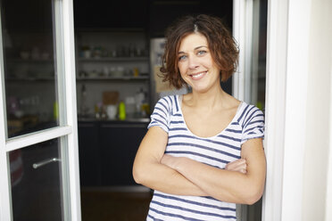 Portrait of content mature woman leaning against open balcony door - PNEF00623