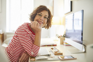 Portrait of content mature woman sitting at desk at home - PNEF00626