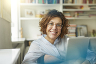 Portrait of content mature woman with tablet at home - PNEF00629