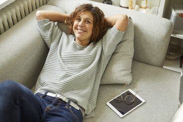 Portrait of smiling mature woman relaxing on couch - PNEF00632
