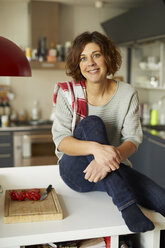 Portrait of smiling mature woman in the kitchen - PNEF00635