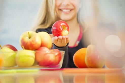 Smiling girl offering an apple - NEKF00035