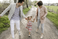 Little girl holding hands of parents while running - KMKF00237