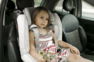 Portrait of little girl sitting in child's seat waiting - KMKF00246