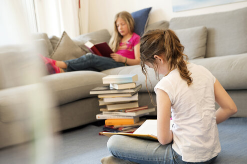 Two girls sitting in the living room reading books - NEKF00041