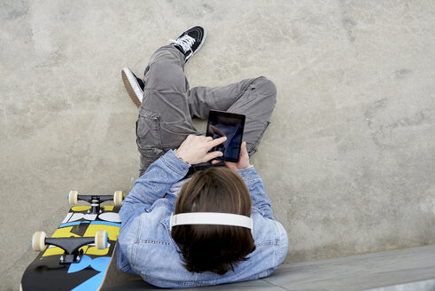 Young man with skateboard sitting on ground, using digital tablet - FMOF00368
