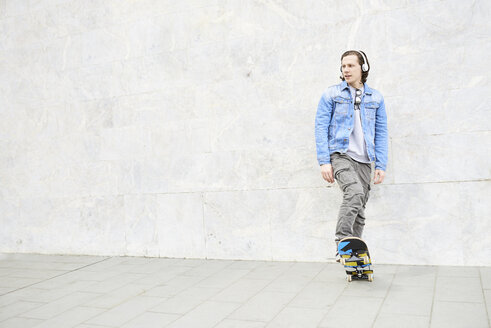 Young man stepping on skateboard, looking away - FMOF00371