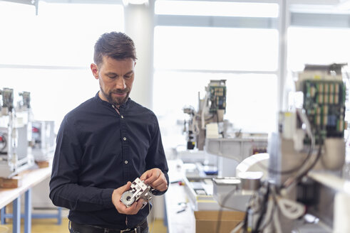 Man in factory examining product - DIGF03975