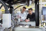 Two men examining machine in factory - DIGF03981