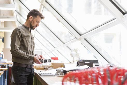 Man in factory examining product - DIGF03996