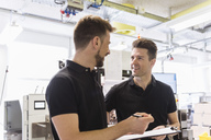 Two men with clipboard talking in factory - DIGF04023
