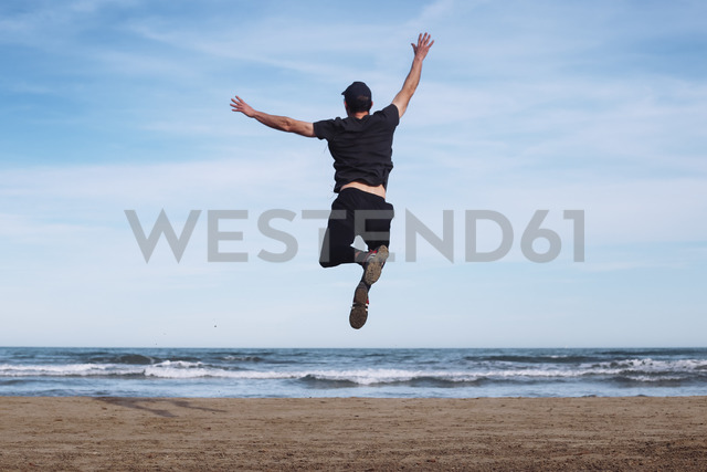 Back view of man jumping in the air on the beach - RTBF01221 - Retales Botijero/Westend61