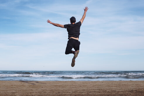 Back view of man jumping in the air on the beach - RTBF01221