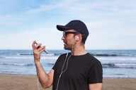 Man using smartphone and earphones on the beach - RTBF01224
