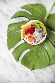 Coconut bowl with variuos fruits, natural yoghurt and seeds on leaf - RTBF01227