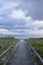 Germany, Ruegen Island, Binz, Baltic Sea, wooden boardwalk to beach in the evening - RUEF01868