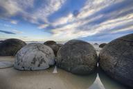 New Zealand, Otago coast, Moeraki Boulders on Koekohe Beach with dramatic sky - RUEF01871