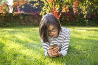 Girl lying on meadow using smartphone - LVF06912
