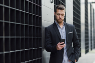 Young businessman looking at his smartphone - JSMF00150