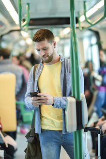 Young man in a subway train looking at his smartphone - JSMF00162