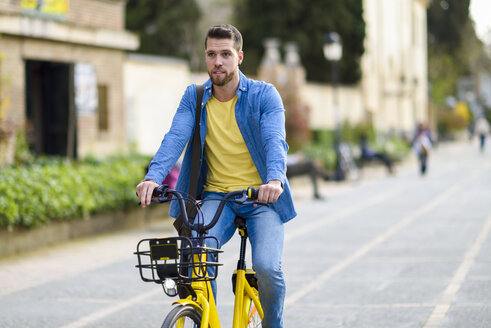 Young man riding rental bike in the city - JSMF00171