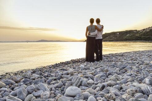 Greece, Pelion, couple enjoying at sunset at beach - MAMF00086