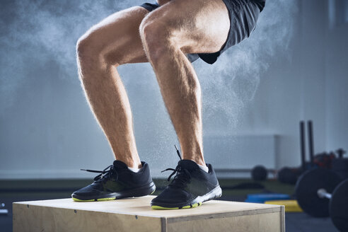 Closeup of man doing box jump exercise at gym - BSZF00305