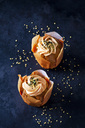 Two carrot cup cakes garnished with  cream topping and sugar granules - CSF29175