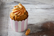 Carrot cup cake garnished with  cream topping, sugar granules and marzipan carrot - CSF29181