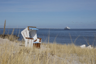 Germany, Schleswig-Holstein, Sylt, List, empty hooded beach chair, cruise ship in the background - WIF03505