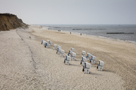 Germany, Schleswig-Holstein, Sylt, beach and empty hooded beach chairs - WIF03511