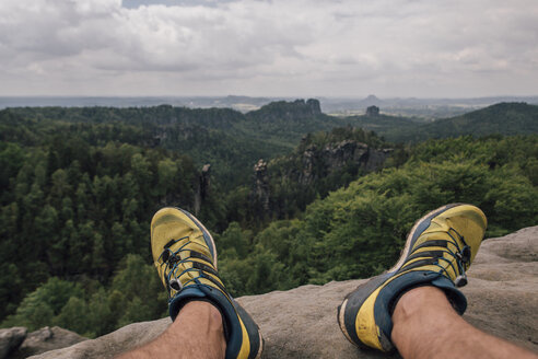 Germany, Saxony, Elbe Sandstone Mountains, man's feet on a hiking trip sitting on rock - GUSF00736