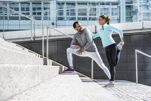Couple doing stretching exercise on stairs in the city - DIGF04036