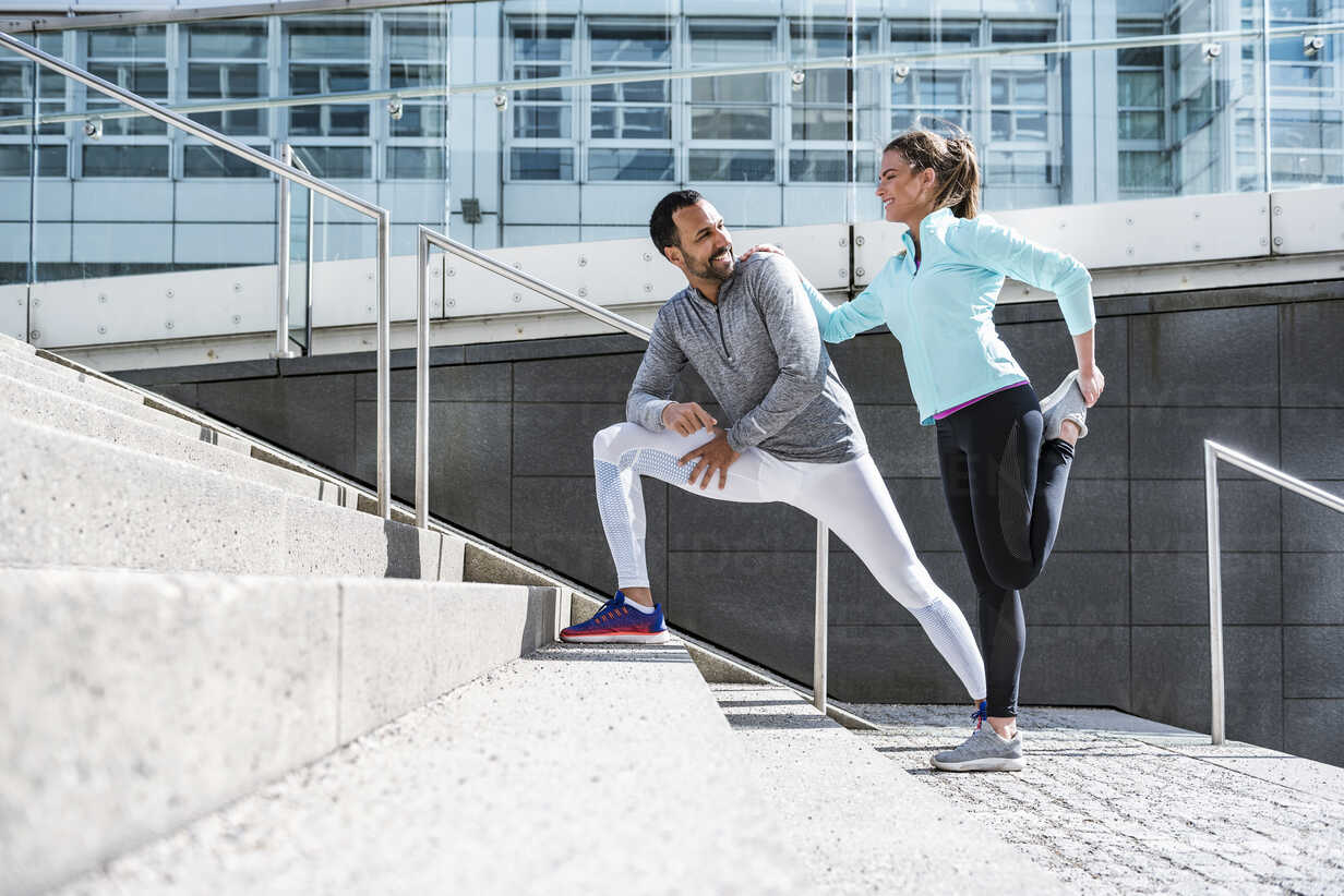 Couple doing stretching exercise on stairs in the city - DIGF04036 - Daniel Ingold/Westend61