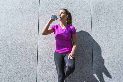 Young woman having a break from exercising drinking from bottle - DIGF04051