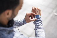 Close-up of athlete checking smartwatch - DIGF04054